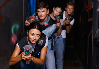 Portrait of happy young friends playing laser tag  game  with laser guns in dark corridor