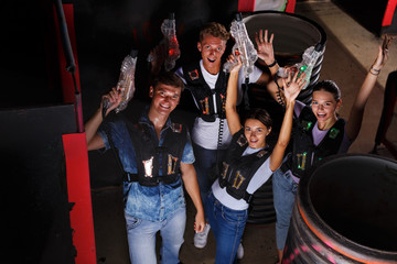 friends playing laser tag  game  with laser guns near tires