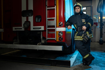 Full-length picture of man firefighter at fire truck