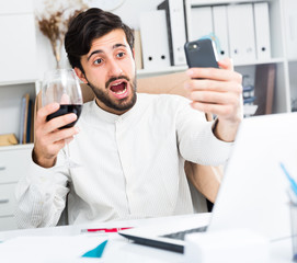 Office worker with glass of wine taking selfie