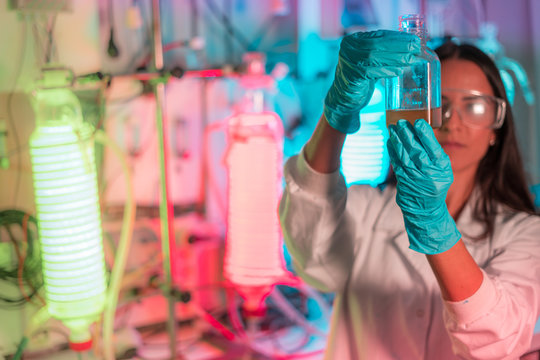 Female scientist working in a biotechnology laboratory with reactors and microalgae cultivation
