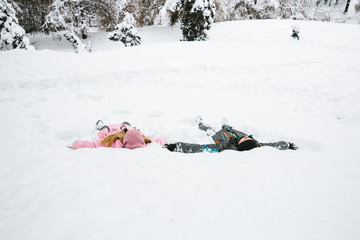 people laying and playing in the snow, making a snow angel on a cold winter day