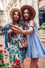 Outdoor portrait of two young beautiful women taking selfie using phone. Girls having fun in city. Best friends