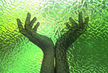 Symbol of peace, hands, the background is thick green glass.