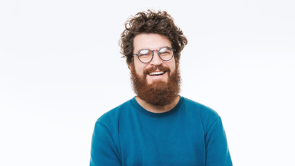 Portrait of smart  bearded man in blue sweater looking at camera and smiling Wall mural