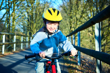 Boy riding his bike on a spring country track.  Road concept for safety and child development