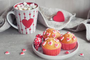 Muffins decorated with sugar hearts and a cup with red heart on light gray background