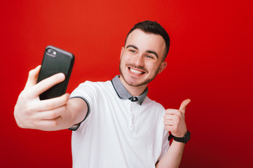 Cheerful young boy is doing a seflie photo and gesturing thumb up