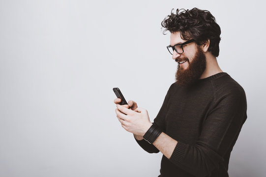 Handsome bearded model is posing with phone in hands over white background