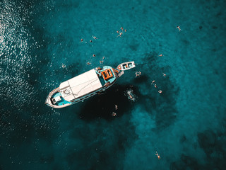 Aerial shot of beautiful blue lagoon at hot summer day with sailing boat. Top view of people swimming around the boat.