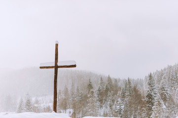 Picture of a cross  in winter season, on winter mountains backgorund