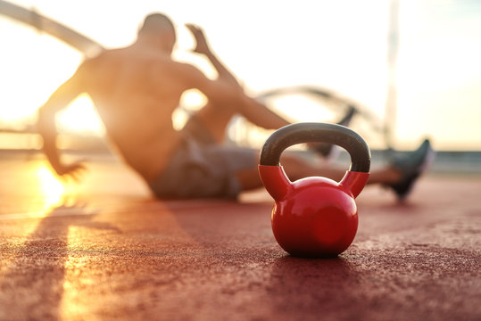 Silhouette of shirtless man doing crunches in the court in the morning. Selective focus on kettlebell.