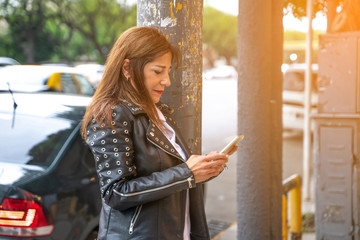 A smiling mature woman in a black leather jacket walking on the street and using her smartphone.