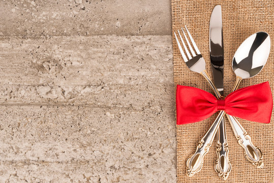 Close up on table settings with a decorative red bow on silverware, directly above.