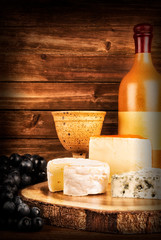 Bottle and glass of wine isolated on a wooden plank in background. Set of cheese on table.