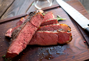 Medium rare ribyey steak cut into pieces on board
