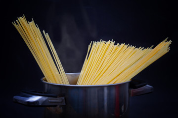 Closeup of spaghetti in pot with boiling water and steam. Dark background.