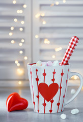 Hot chocolate with marshmallows, red heart on the cup, winter background with ceramic heart and lights