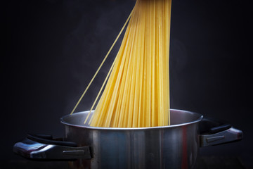 Preparing spaghetti for dinner. Putting spaghetti in pot with boiling water and steam. Dark background.