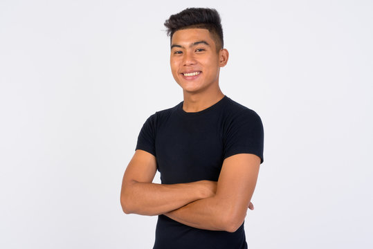 Young happy Asian man with arms crossed against white background