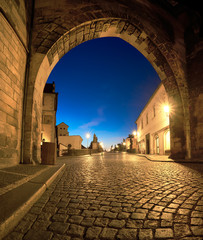 Romantic Prague at dawn, entrance to Charles Bridge through the illuminated arch of Lesser Town Bridge Tower