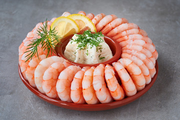Close-up on shrimp ring with fresh cheese, dill and lemon on light concrete
