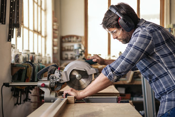 Carpenter sawing wood with a mitre saw in his workshop