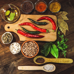 Hot chili pepper and spices on wooden background.