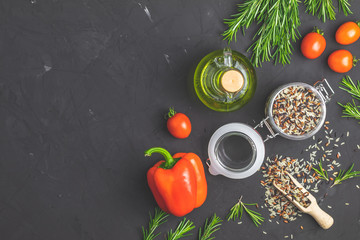 Rice mix in glass jar and fresh vegetables on black stone concrete textured surface