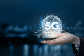 A hand is holding a digital sphere with 5G sign inside.