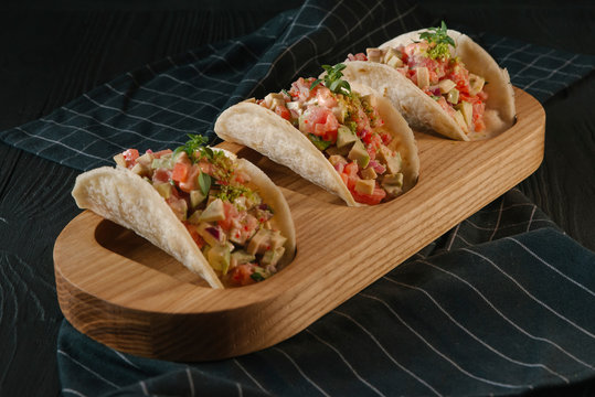 Close up of tacos with guacamole sauce served in wooden tray on table