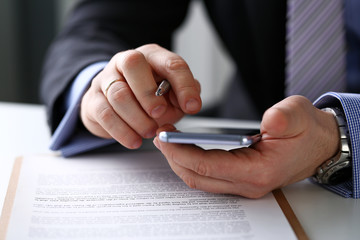 Male arm in suit hold phone and silver pen at workplace closeup