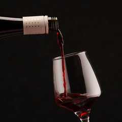 Close-up of red wine pouring in glass against black background
