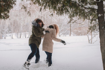 Playful lesbian couple standing on snow covered field against trees in park