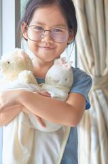 Portrait of smiling girl wearing eyeglasses embracing teddy bears at home