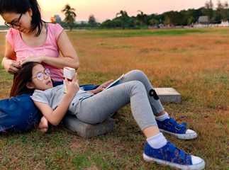 Daughter lying on mother's laps during sunset