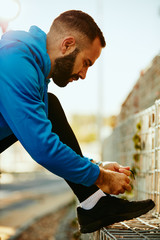 Young bearded sporty man in sportswear tying shoelace with leg on the fence. Outdoor sport concept.