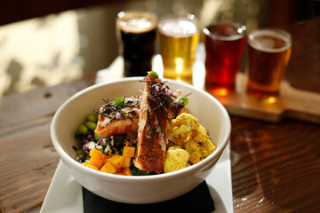 High angle view of food in bowl with beer glasses on wooden table
