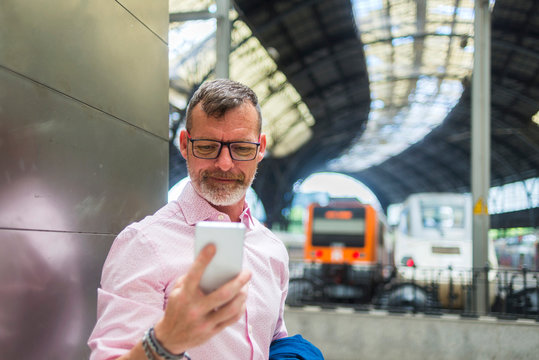 Businessman using smart phone while standing by wall at railroad station platform