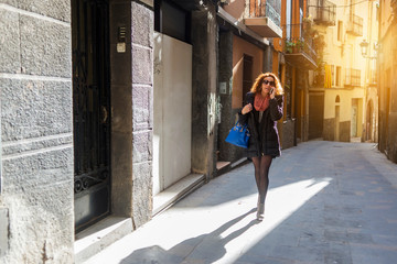 Woman wearing sunglasses talking on smart phone while walking at alley amidst buildings in city