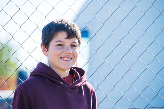 Portrait of smiling boy standing against chainlink fence during sunny day