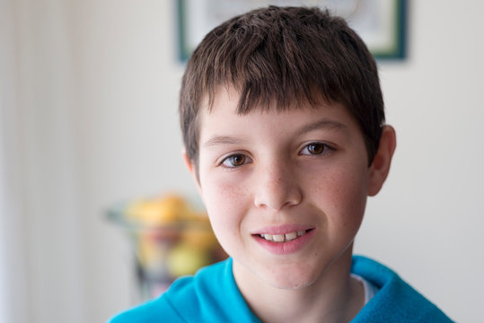 Close-up portrait of smiling boy standing against wall at home