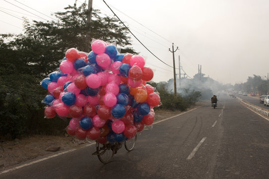 Colorful balls tied to bicycle on road against clear sky