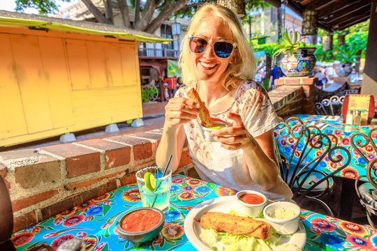 Joyful blonde woman puts enchilada in chili sauce, at typical Mexican food, at traditional restaurant of El Pueblo, Olvera street, Los Angeles Downtown State Historic Park, California, United States.