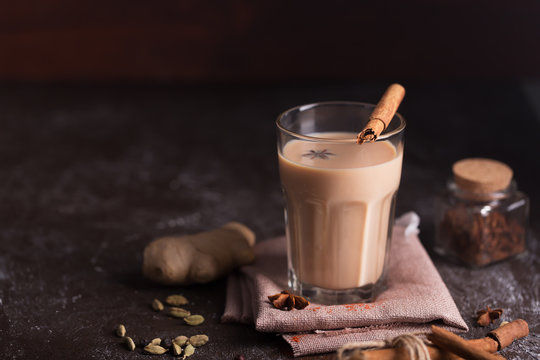 Masala chai tea on the dark background. Hot indian beverage with spices. Image with copy space