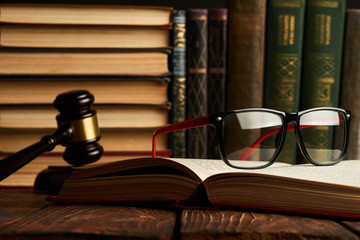 Judge gavel and legal book collection with eyeglasses on wooden