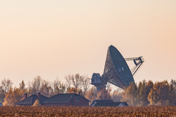 Military radar at sunset located in the meadow.