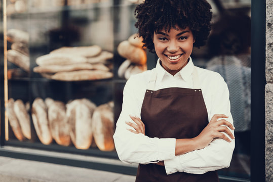 Attractive lady standing near bakery shop and smiling