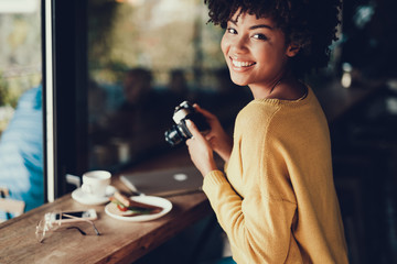Cheerful lady holding her camera in hands