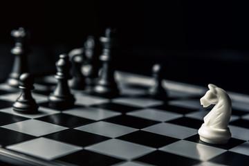 Chess board. White horse threatens black opponent's chess